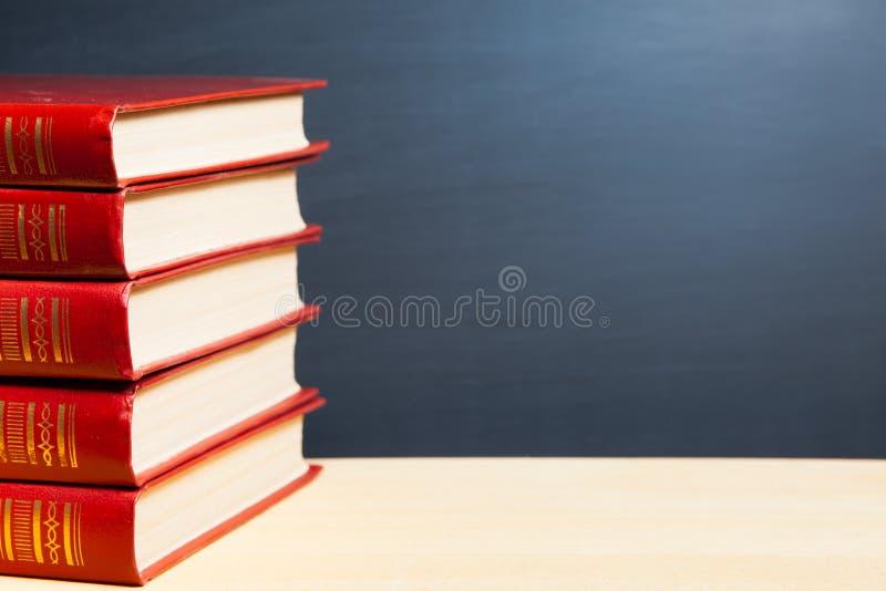 Röda böcker och svart tavla royaltyfri fotografi