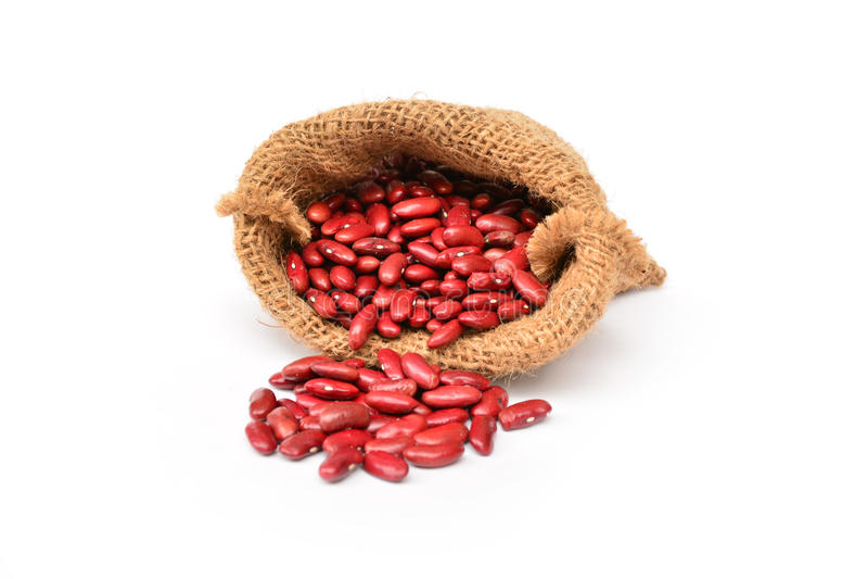 Röda bönor i säcken som isoleras på vit arkivfoto