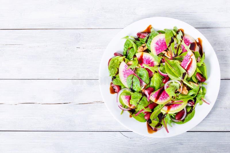 Röda bönor, vattenmelonrädisa, grönsallatsidor, valnötter sallad, cl arkivfoto