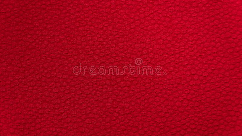 Röda bakgrundstygtextiler med en liten broderimodell royaltyfri fotografi