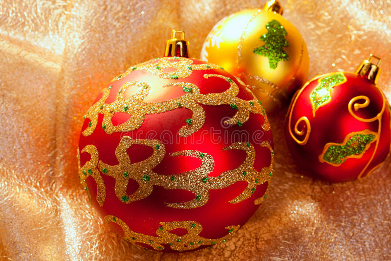 Röda baubles för jul på guld- tyg royaltyfri fotografi