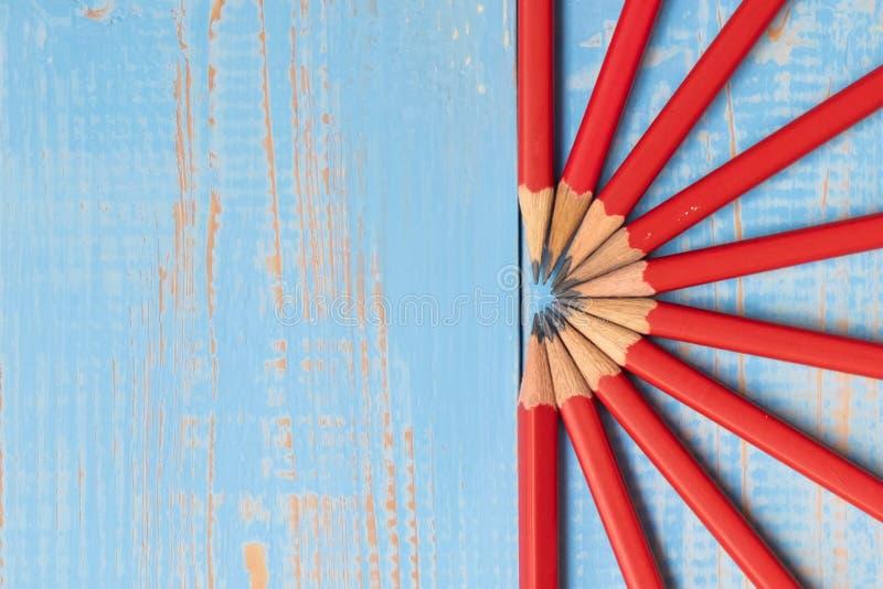 Röda blyertspennor på blå träbakgrund arkivfoto