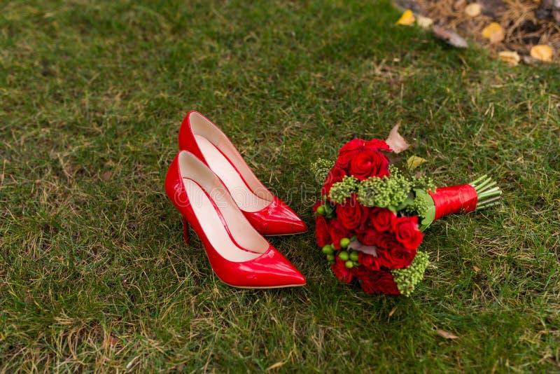 Röda bröllopskor för kvinnligt mode med buketten för brud` s av röda rosor och gröna bär på bakgrund för grönt gräs arkivbilder