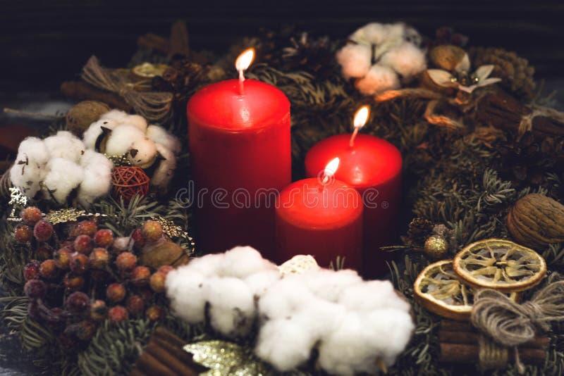 Röda brinnande julstearinljus i en sörjakrans royaltyfria bilder