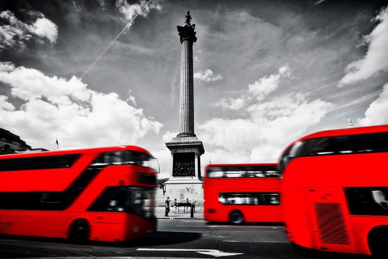 Röda bussar i rörelse på Trafalgar Square i London, UK kolonn nelson s royaltyfri bild