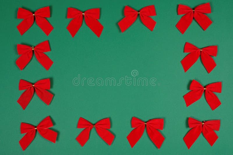 Röda Cristmas pilbågar på grön bakgrund royaltyfria bilder