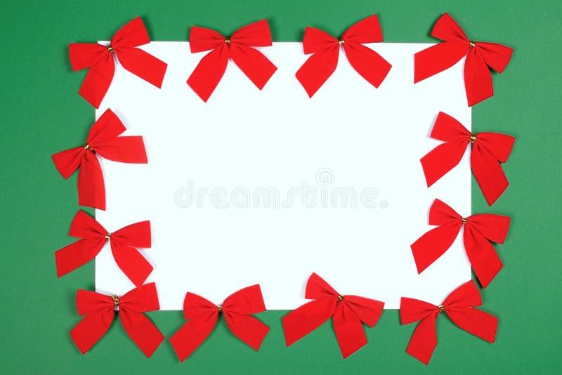 Röda Cristmas pilbågar på grön bakgrund arkivfoto