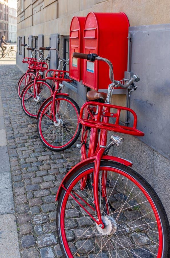Röda cyklar och brevlåda i Copenhangen med en cyklist i backgroen arkivbilder