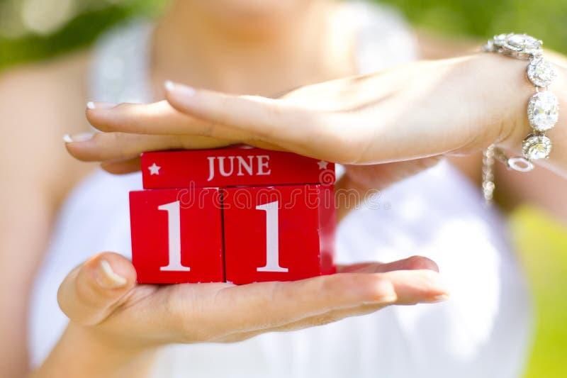Röda dekorativa kuber med ` för nummer` 11 och ord`-juni ` i händer av flickan royaltyfri fotografi