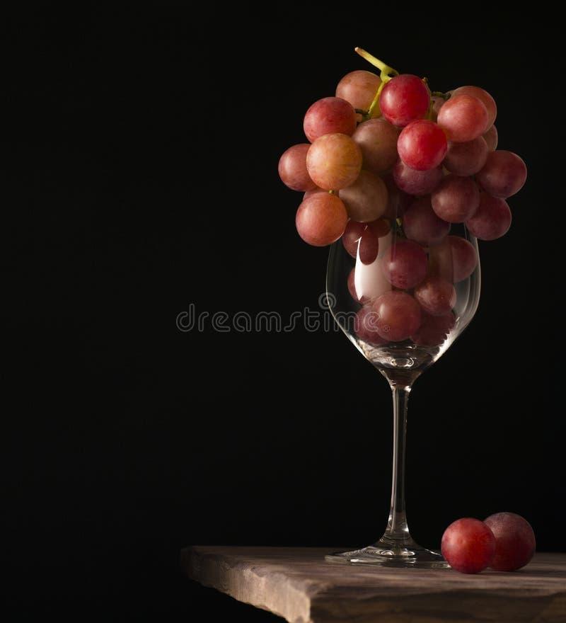 Röda druvor i vinexponeringsglas på svart bakgrund arkivfoton