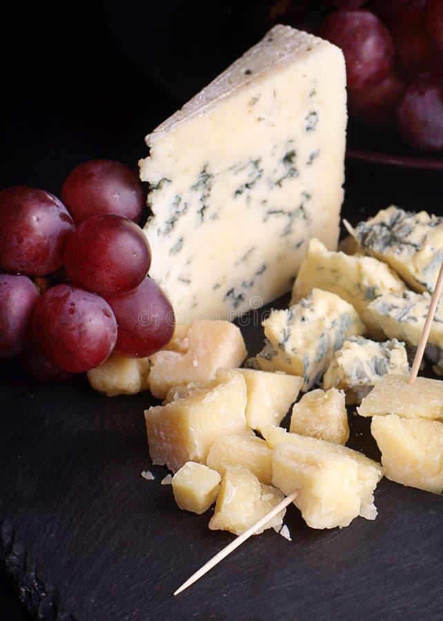 Röda druvor och ost av olika variationer på ett mörker kritiserar arkivfoto