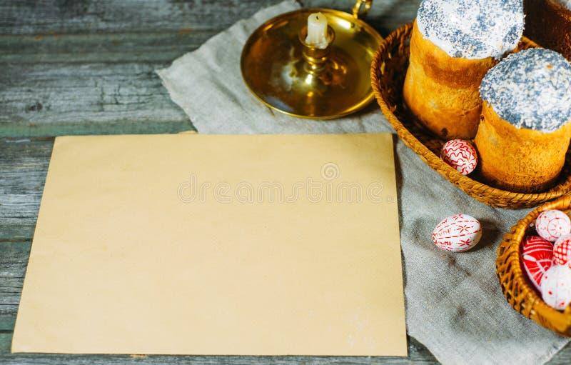 Röda easter ägg med den folk ukrainska modellen lägger in i korg bredvid easter kakor och arket av rent papper på gammal träbakgr royaltyfri fotografi