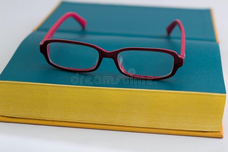 Röda exponeringsglas och guld- bok royaltyfria bilder