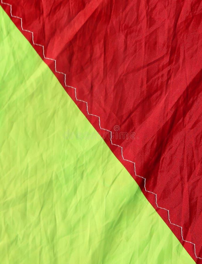 Röda för nylontyg itu delade ljusa och gula färger i halva royaltyfria foton