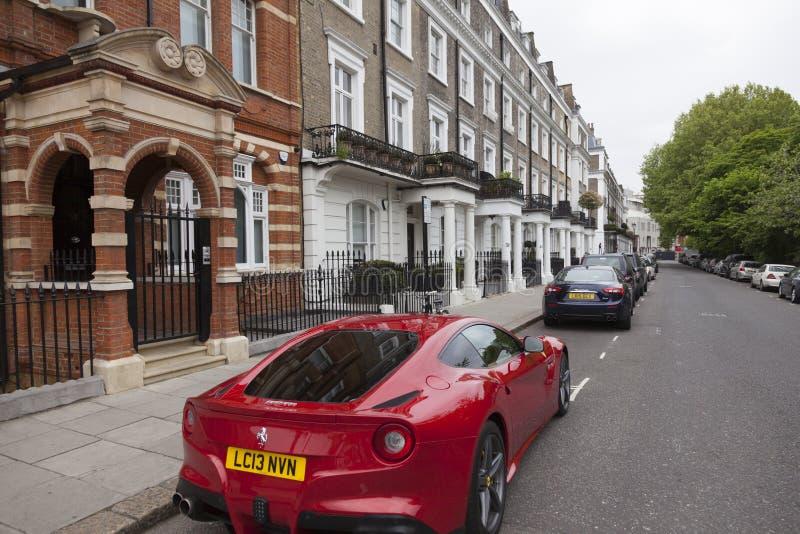 Röda ferrari på den dyra gatan i london kensington royaltyfria foton
