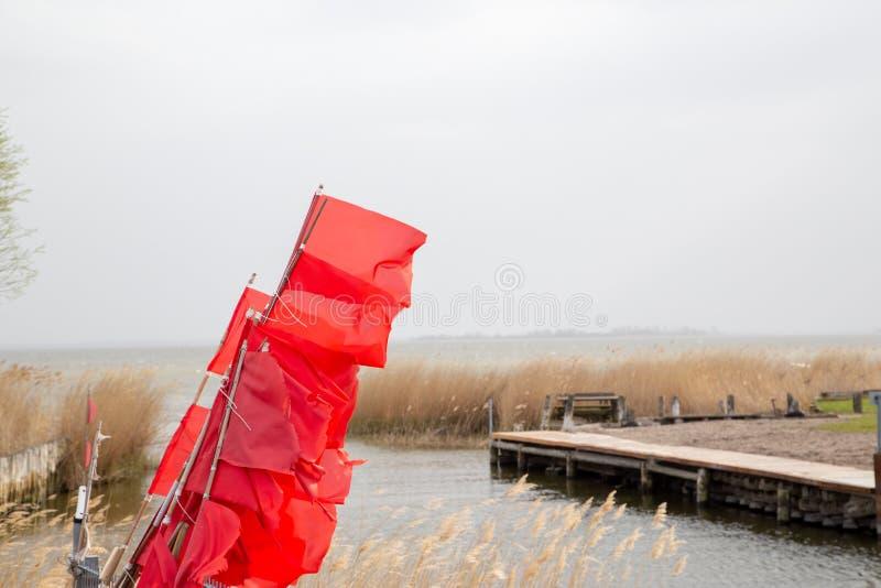 Röda flaggor av fisknät på den lilla porten av Zempin på ön av Usedom arkivfoton
