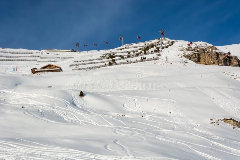 Röda gondoler skidar in semesterorten Serfaus Fiss Ladis i Österrike med sn royaltyfri bild