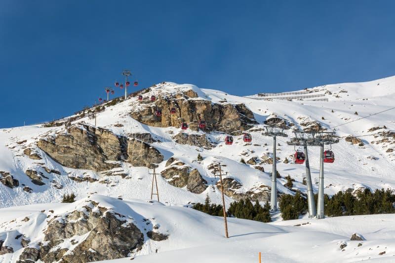 Röda gondoler skidar in semesterorten Serfaus Fiss Ladis i Österrike med sn arkivbild