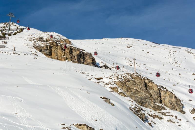 Röda gondoler skidar in semesterorten Serfaus Fiss Ladis i Österrike med sn royaltyfria bilder