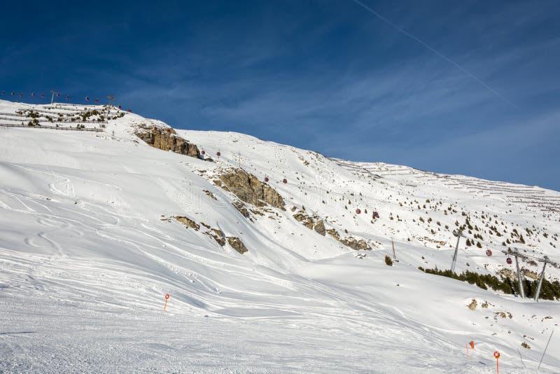 Röda gondoler skidar in semesterorten Serfaus Fiss Ladis i Österrike med sn royaltyfri fotografi