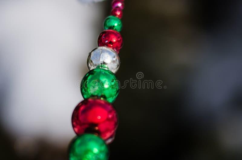 Röda, gröna och för silverjulprydnad pärlor som dekorerar ett snöig utomhus- träd fotografering för bildbyråer