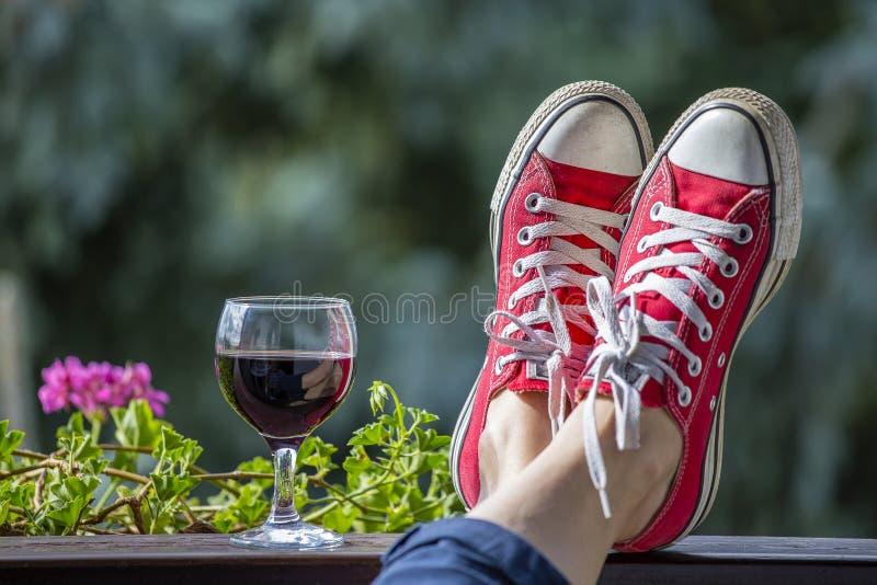 Röda gymnastikskor på benen av en kvinna och ett exponeringsglas av vin mot bakgrunden av naturen arkivfoton