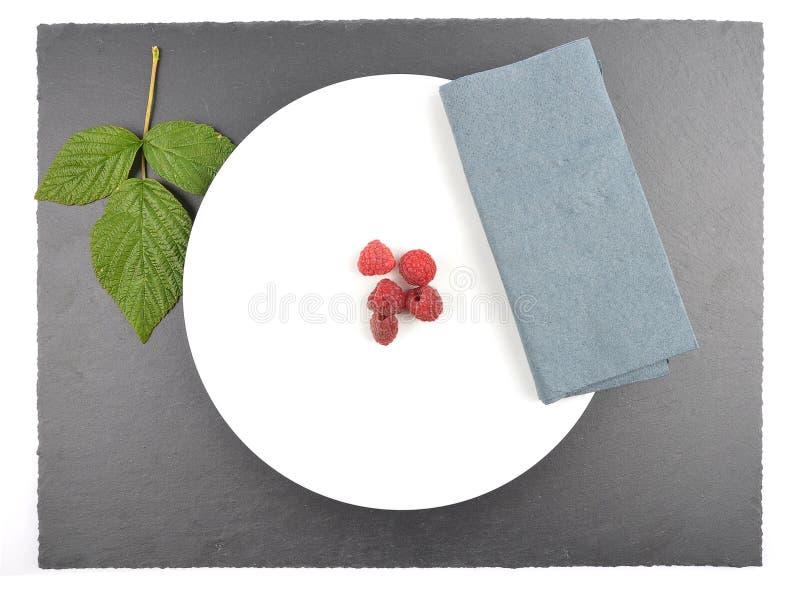 Röda hallon på plattan och skiffer fotografering för bildbyråer