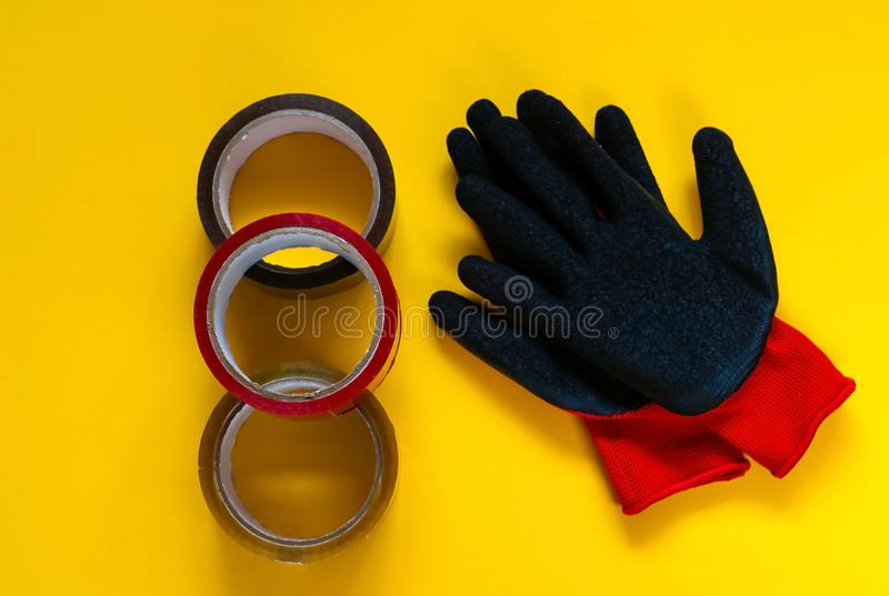 röda handskar och kulör tejp, tillbehör för att förpacka på gul bakgrund, kopieringsutrymme arkivbild