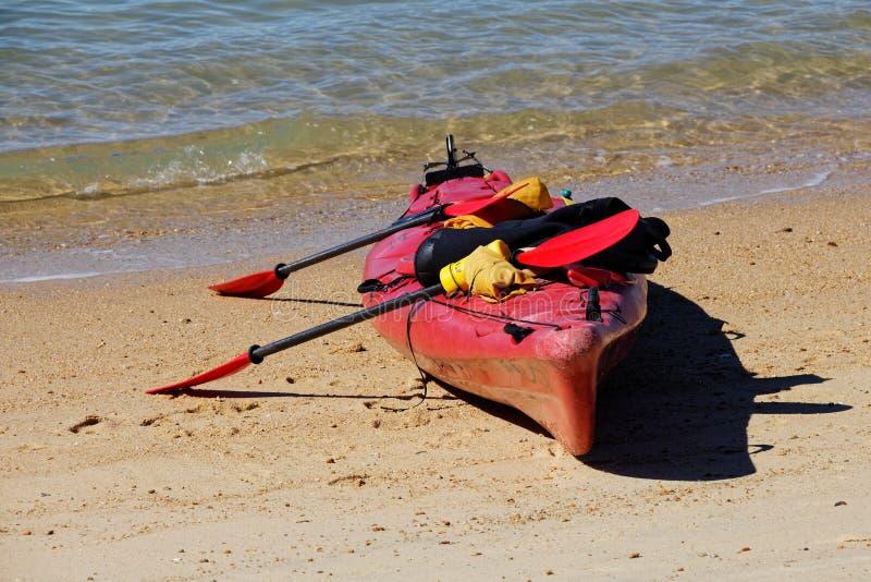 Röda havetkajak på stranden fotografering för bildbyråer