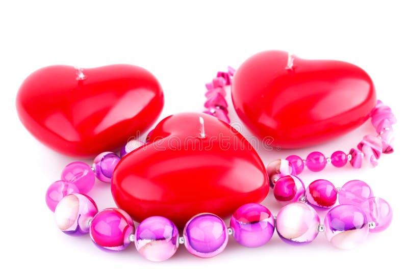 Röda hjärtastearinljus och rosa halsband royaltyfri fotografi
