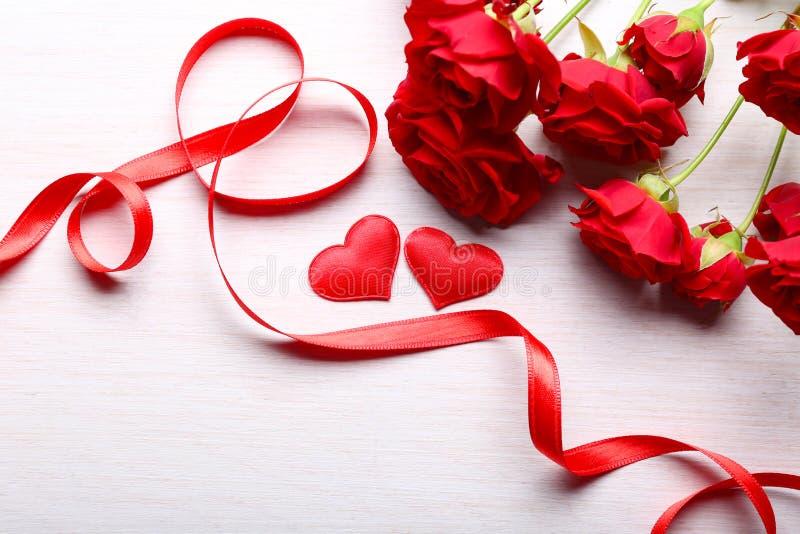 Röda hjärtor, band och härliga rosor på trätabellen royaltyfria bilder
