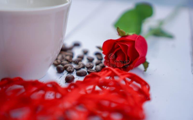 Röda hjärtor och blommor på ett vitt trägolv med utrymme, idéförälskelse eller dagen av förälskelsevalentindagen fotografering för bildbyråer
