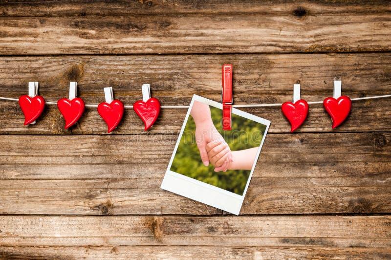 Röda hjärtor och foto, som två händer rymmer sig tillgänglig vektor för valentiner för kortdagmapp royaltyfri foto