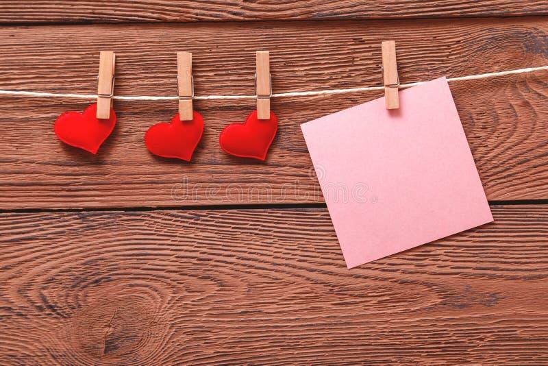 Röda hjärtor och klistermärke på träbakgrund Bakgrund för dag för valentin` s Klistermärke och små hjärtor på klädnypor royaltyfri foto