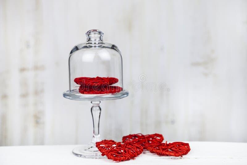 Röda hjärtor på en glass maträtt arkivfoton