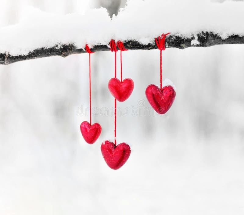 Röda hjärtor på snöig trädfilial i vinter För valentindag för ferier lyckligt begrepp för förälskelse för hjärta för beröm arkivbilder
