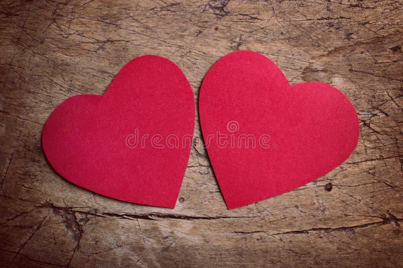 Röda hjärtor på trätabellen arkivbild