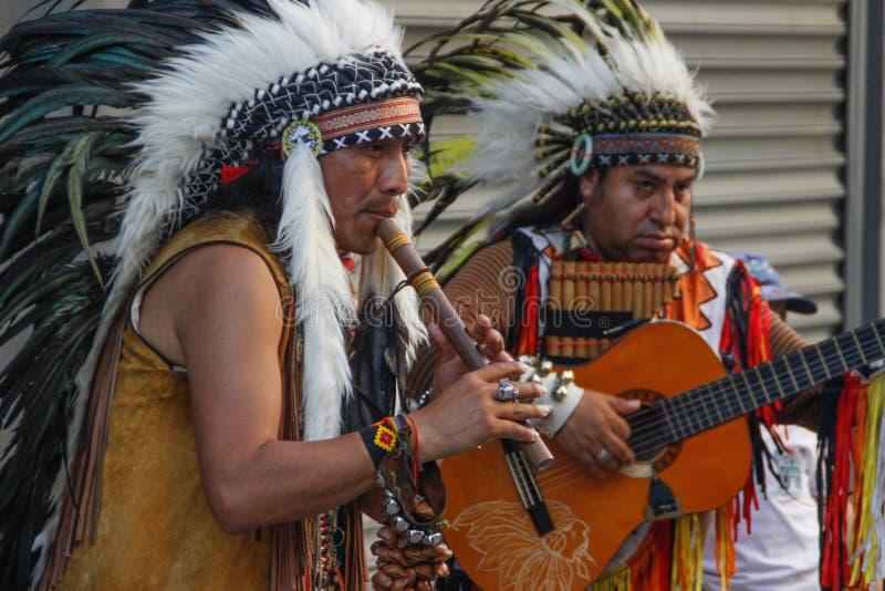 Röda indierindianer spelar flöjten och gitarren i fjäderhuvudbonader arkivfoto