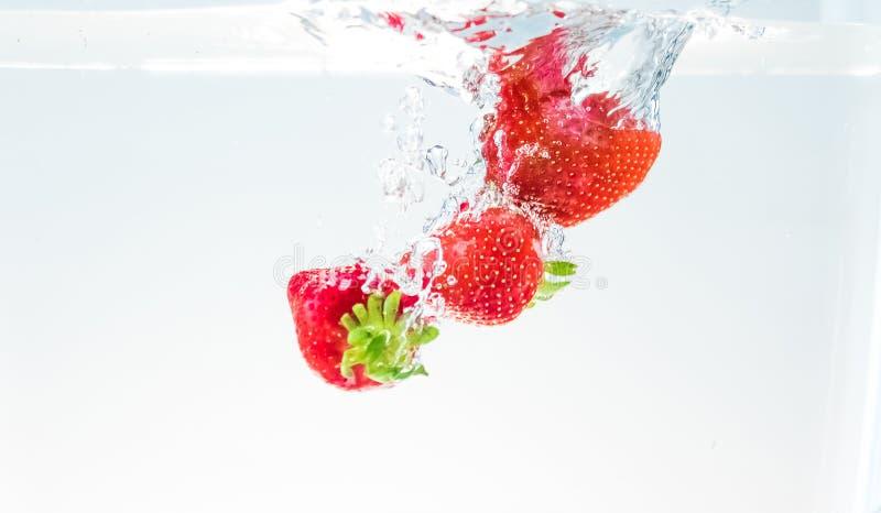 Röda jordgubbar för ny frukt som faller in i vatten med färgstänk på vit bakgrund, jordgubben för hälsa och, bantar, näring arkivfoton