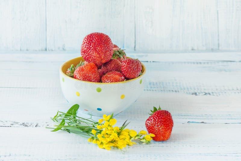 Röda jordgubbar, mogna lögner i en vit kopp med mycket små gula blommor på blå träbakgrund kopiera avstånd royaltyfria bilder