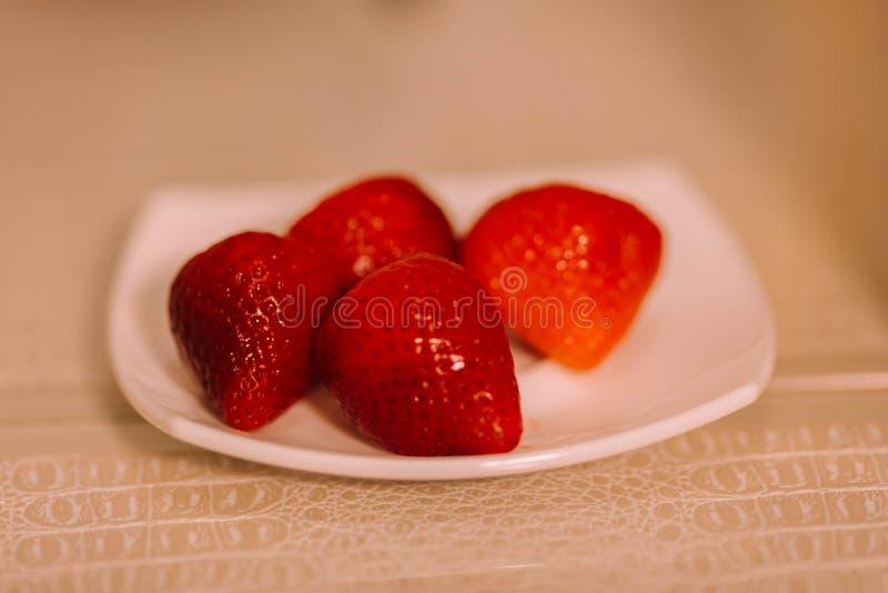 Röda jordgubbar på ett vitt tefat på tabellen royaltyfria bilder
