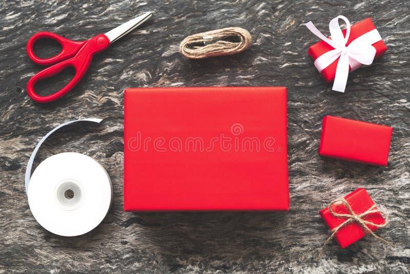 Röda julgåvaaskar framlägger att förbereda handgjord garnering a royaltyfria foton