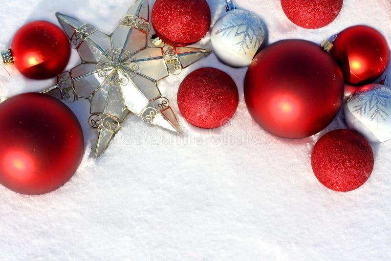 Röda julkulor och stjärna i den vita snögränsen fotografering för bildbyråer