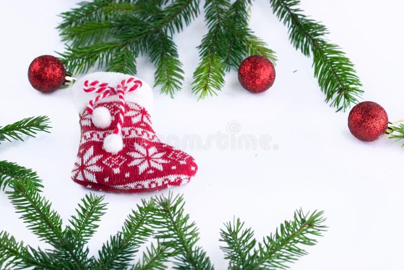 Röda julstrumpasocka- och garneringbollar på vit backgr royaltyfria bilder