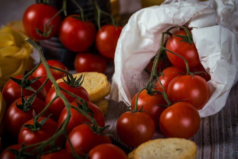 Röda körsbärsröda tomater i pappers- påse på tappningträtabellen med tagliatelle och bruschetta arkivfoto
