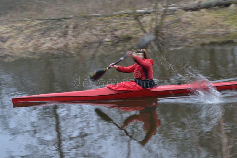 Röda kajakflöten längs floden i tidig vår arkivfoton