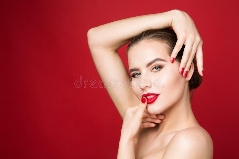 Röda kanter och spikar, kvinnaskönhetsminket, röd läppstift och polsk härlig flickaframsidamakeup royaltyfria foton