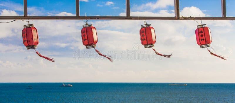 Röda kinesiska pappers- lyktor mot en blå himmel och ett hav royaltyfri bild