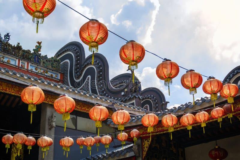 Röda kinesiska pappers- lyktor som hänger på bakgrunden av blå himmel med moln royaltyfri foto