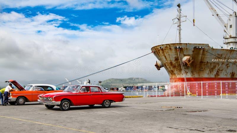 Röda klassiska amerikanska bilar framme av det rostiga skeppet i hamn i Santiago de Cuba royaltyfri fotografi